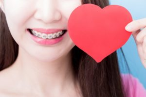 Woman with adult braces in Milton holds paper Valentine heart