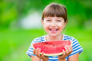 Girl with watermelon and braces in summer