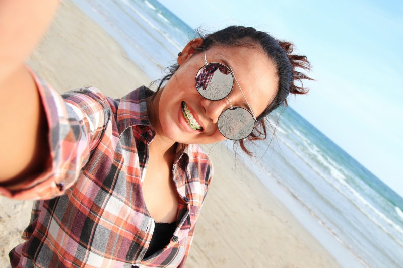 Woman with braces taking a selfie on the beach